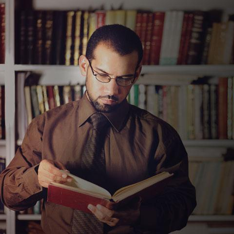 Image of man in brown shirt and tie reading a book in a library